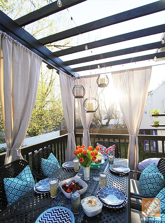 Make a covered outdoor dining area with elegant draperies.