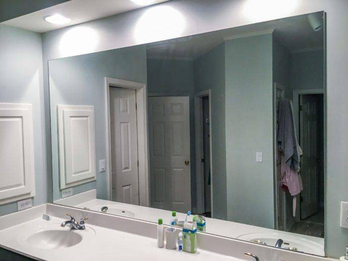Builder's grade mirror in the bathroom.