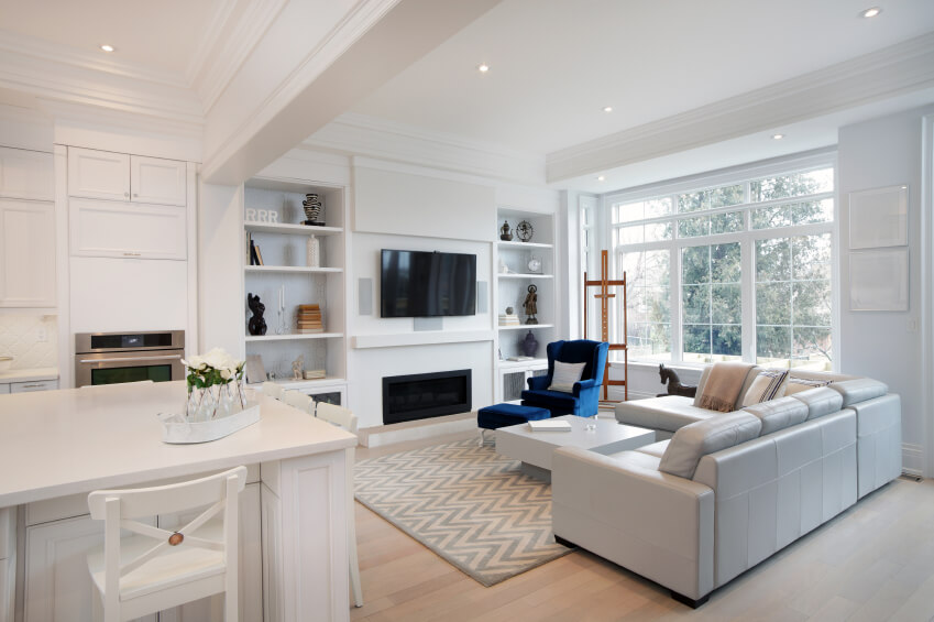 Open concept living room and kitchen in white with blue accents.